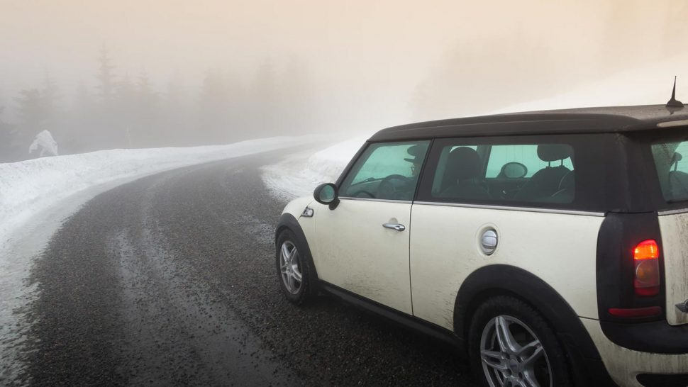 white mini car driving on a snow covered road in the cold