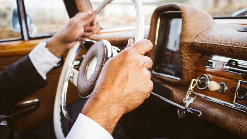 old Driver with their hands on the wheel of a car